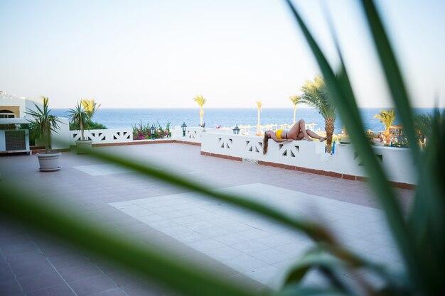Linda garota com cabelo loiro e um maiô amarelo relaxando em um terraço contra o mar