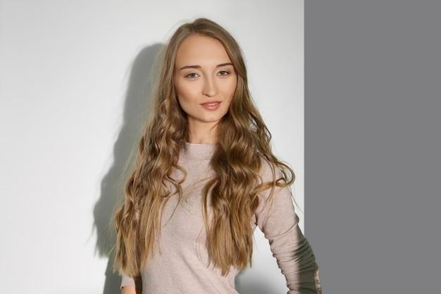 Linda garota com cabelo loiro longo encaracolado. maquiagem natural e pele perfeita.