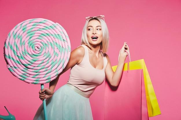 Linda garota com cabelo loiro usando blusa e saia em pé com enormes pirulitos doces e segurando sacolas de compras coloridas