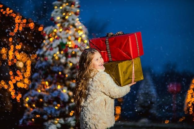 Linda garota com cabelo longo encaracolado em casaco bege segurando grandes presentes contra as decorações de natal. copie o espaço.