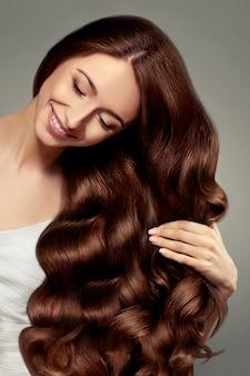 Linda garota com cabelo longo ondulado e brilhante