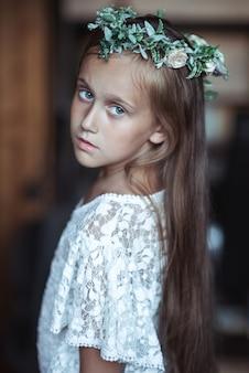 Linda garota com cabelo muito comprido e uma linda coroa de flores na cabeça