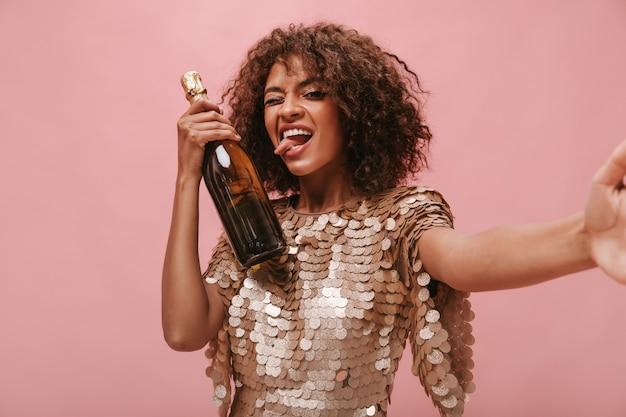 Linda garota com cabelo ondulado morena em um vestido brilhante piscando mostrando a língua, segurando a garrafa com a bebida e tirando foto na parede rosa.