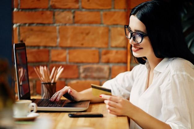 Linda garota com cabelo preto, usando óculos, sentado no café com laptop, telefone celular, cartão de crédito e xícara de café, conceito freelance, camisa branca.