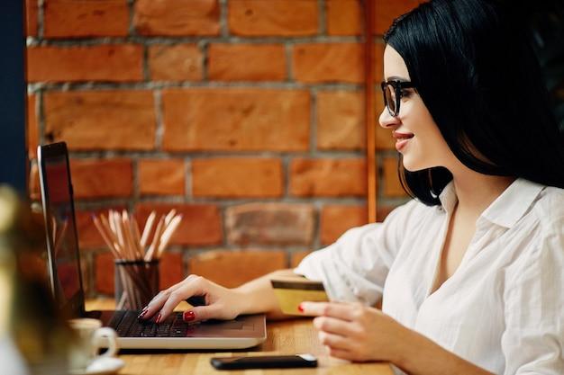 Linda garota com cabelo preto, usando óculos, sentado no café com laptop, telefone celular, cartão de crédito e xícara de café, conceito freelance, compras online, camisa branca.