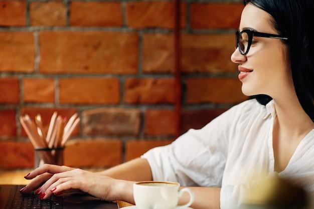 Linda garota com cabelo preto, usando óculos, sentado no café com o laptop e a xícara de café, conceito freelance, retrato, vestindo camisa branca.