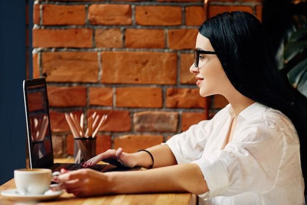 Linda garota com cabelo preto, usando óculos, sentado no café com o laptop e uma xícara de café, conceito freelance, retrato, vestindo camisa branca.