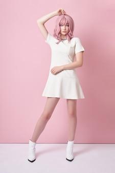 Linda garota com cabelo rosa, coloração de cabelo. mulher de anime bonito fica em um fundo rosa em um vestido branco curto. cabelo colorido, penteado perfeito