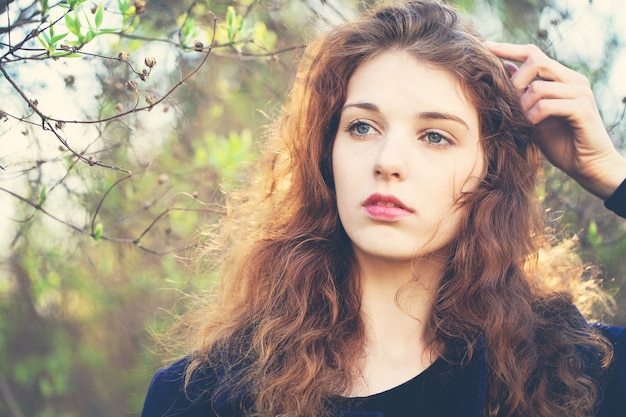 Linda garota com cabelo ruivo cacheado ao ar livre à luz do sol