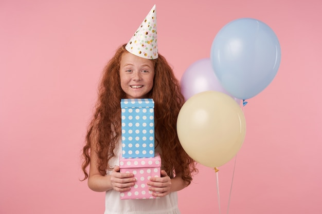 Linda garota com cabelo ruivo cacheado em um vestido branco e boné de aniversário feliz olhando para a câmera com caixas de presente nas mãos, em pé contra um fundo rosa com um largo sorriso, expressa verdadeiras emoções positivas