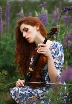 Linda garota com cabelo ruivo e vestido azul segurando o violino no campo de flores da natureza.