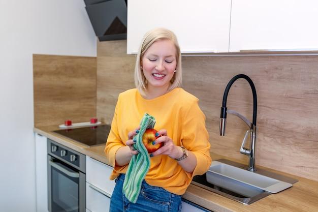 Linda garota com cabelo vermelho loiro chicoteando sua maçã com toalha de cozinha. jovem mulher que limpa sua fruta em sua cozinha. consumo diário de vitaminas com frutas
