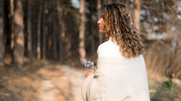 Linda garota com cabelos cacheados na floresta