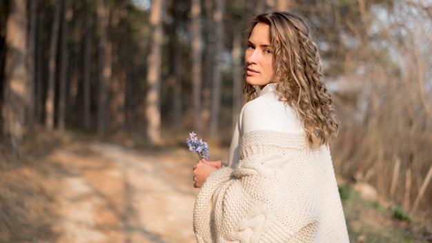 Linda garota com cabelos cacheados, segurando uma flor