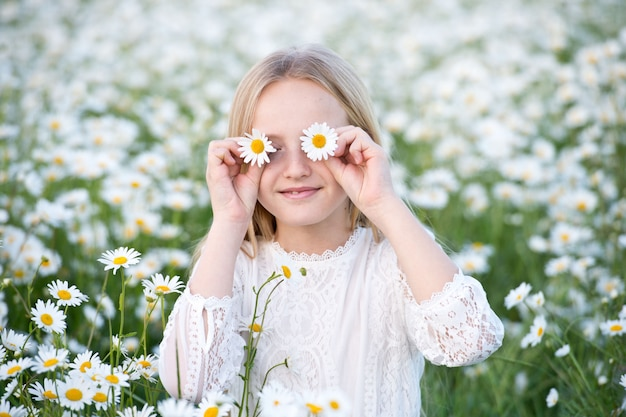 Linda garota com cabelos loiros no campo de camomila. linda menina com coroa de camomila em campo de florescência no verão.