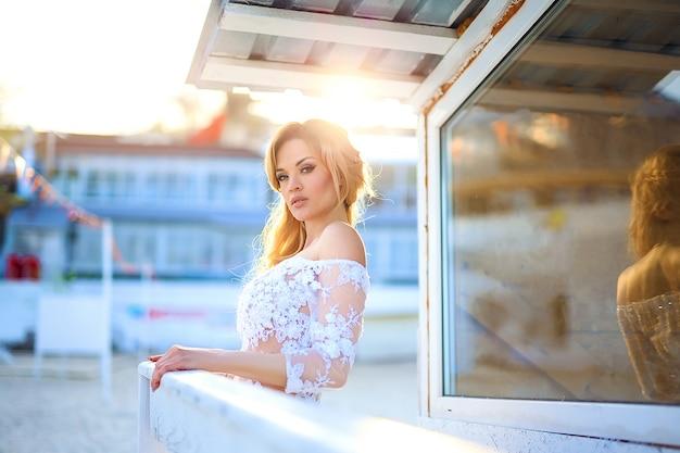Linda garota com cabelos loiros no vestido elegante laço posando besi