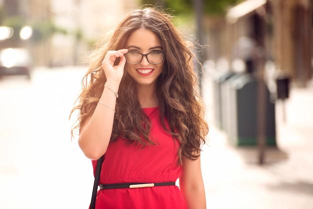 Linda garota com cabelos longos e óculos sorrindo na rua