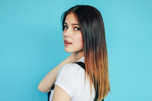 Linda garota com cabelos longos escuros, vestindo camiseta branca isolada em azul