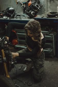 Linda garota com cabelos longos na garagem consertando uma moto