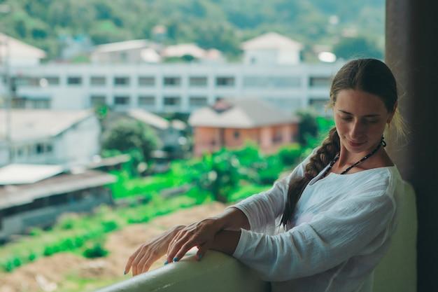 Linda garota com cabelos longos, se aquecendo no vestido branco na varanda do hotel com vista para plantas tropicais.