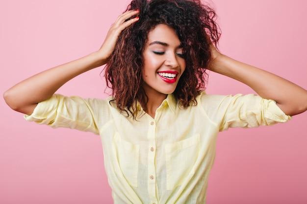 Linda garota com cachos castanhos-escuros se divertindo durante. feliz mulher negra usa elegante camisa amarela.