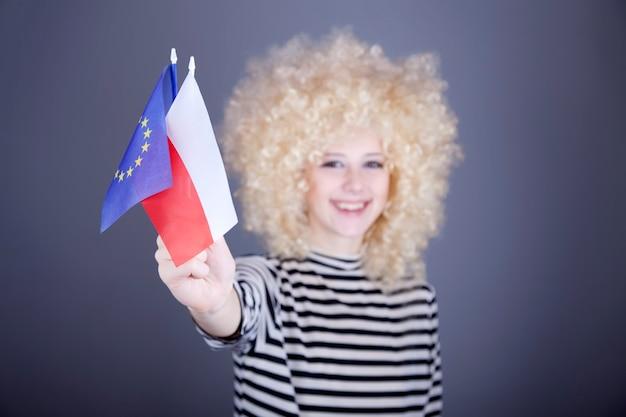 Linda garota com cachos mostra a bandeira da união europeia e a polônia.