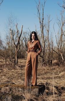 Linda garota com calças marrons e uma camisa de couro em um dia ensolarado