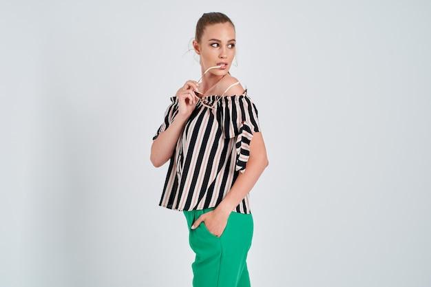 Linda garota com camisa listrada e calça verde isolada no fundo branco