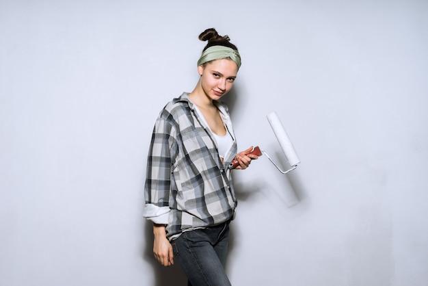 Linda garota com camisa xadrez pinta a parede com um cilindro na cor branca, fazendo reparos