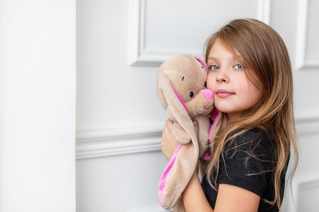 Linda garota com carinho e amor abraça um brinquedo de coelho de pelúcia contra uma parede branca e olha para a câmera