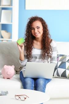 Linda garota com cartão de crédito, cofrinho e laptop no sofá
