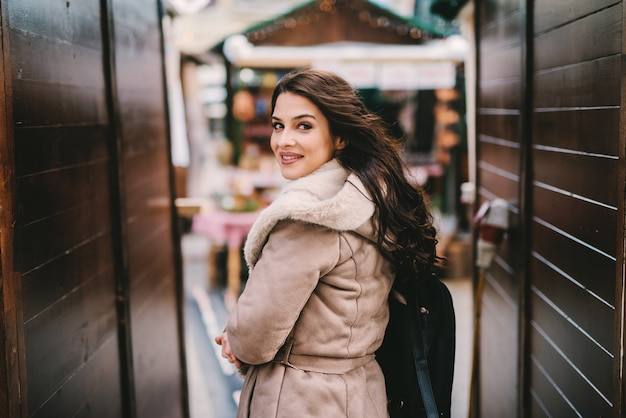 Linda garota com casaco de inverno em pé na passagem da rua. olhando para a câmera. linda rua decorada de natal.