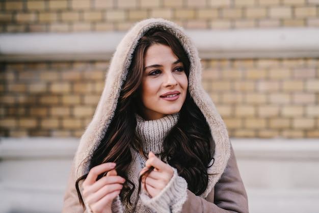 Linda garota com casaco de inverno em pé na rua e aproveitando em um bom dia de inverno. desviando o olhar com um sorriso no rosto.