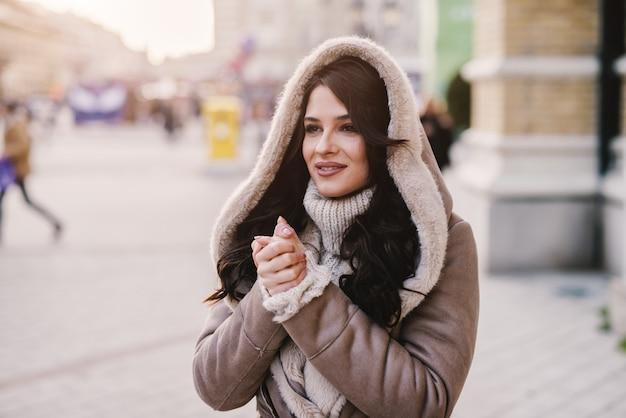Linda garota com casaco de inverno em pé na rua e aquecendo as mãos.