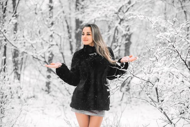 Linda garota com casaco de pele e vestido com as pernas nuas no inverno em um bosque nevado pega neve com as mãos