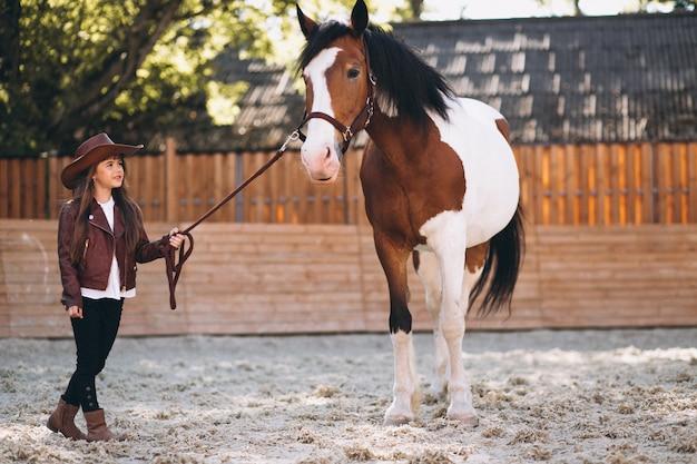 Linda garota com cavalo no rancho