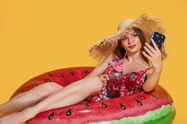 Linda garota com chapéu de palha de vestido de verão com forma de anel inflável de melancia com cocktai fresco.