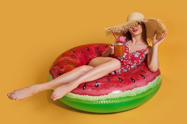 Linda garota com chapéu de palha de vestido de verão, sente-se no colchão de ar em forma de círculo de melancia com pau.