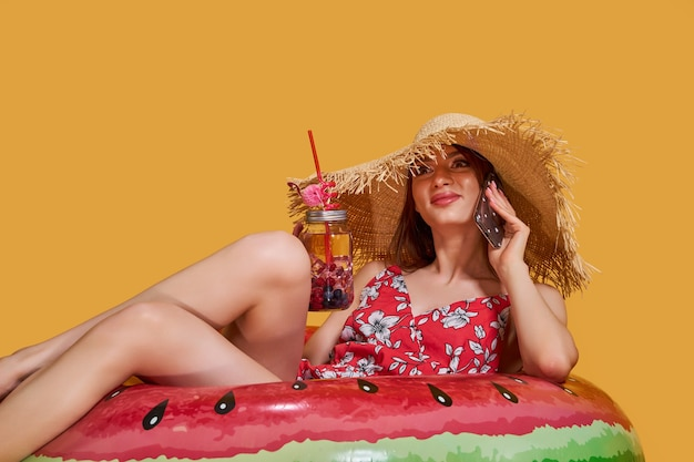 Linda garota com chapéu de palha vestido de verão sentar no colchão de ar em forma de círculo de melancia e beber ...