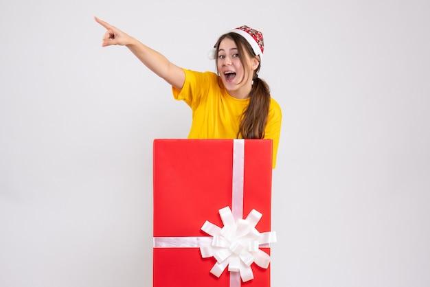 Linda garota com chapéu de papai noel apontando para algo atrás de um grande presente de natal