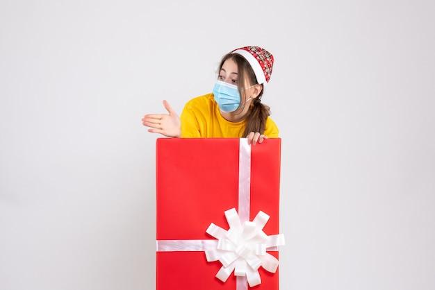 Linda garota com chapéu de papai noel dando a mão em pé atrás de um grande presente de natal.