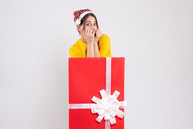 Linda garota com chapéu de papai noel em frente a um grande presente de natal