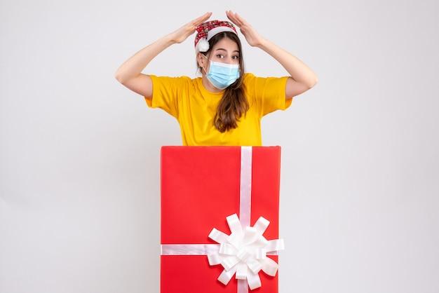 Linda garota com chapéu de papai noel fazendo telhado com as mãos em pé atrás de um grande presente de natal