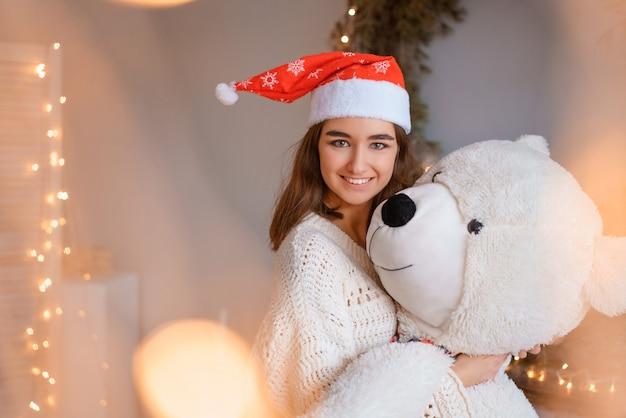 Linda garota com chapéu de papai noel segurando um urso de brinquedo