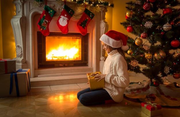 Linda garota com chapéu de papai noel sentada com um presente de natal na lareira