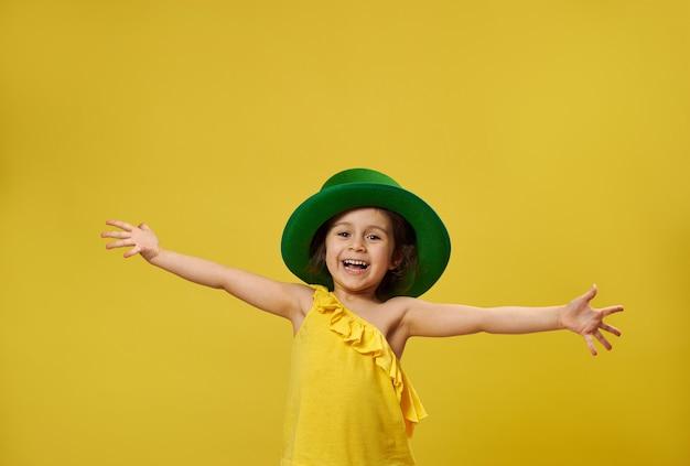 Linda garota com chapéu irlandês de duende verde abre as mãos e sorri para a câmera, posando em uma superfície amarela