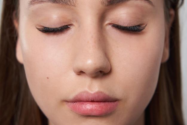 Linda garota com cílios estendidos e olhos fechados