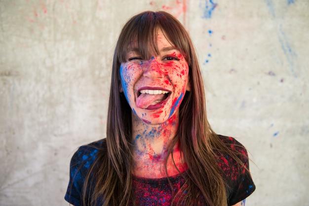 Linda garota com cor holi tirando a língua