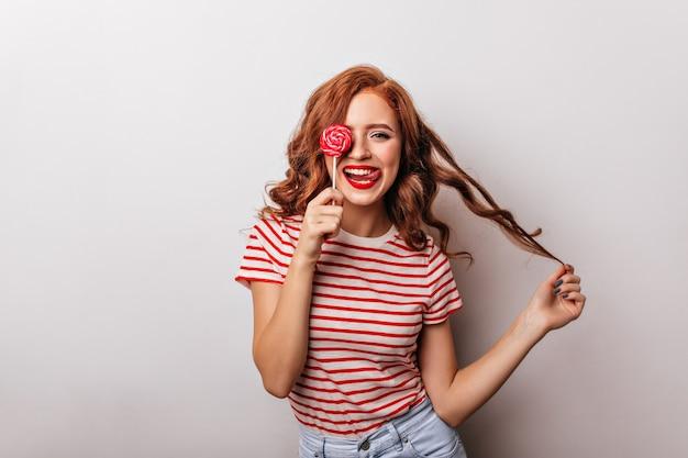 Linda garota com doces brincando com seus cabelos cacheados. graciosa senhora de cabelos compridos com pirulito.