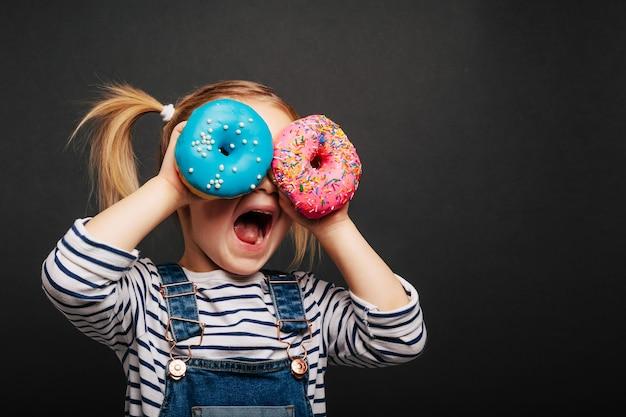 Linda garota com donuts nas mãos